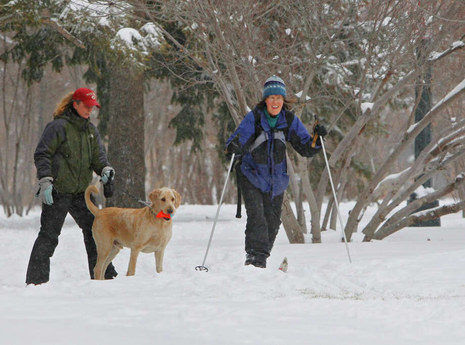 Kathy Hoefer, right, cross country sks past a woman walking her dog in a Denver park on Friday, Feb. 3, 2012. A snow storm dumped 10 inches of snow on the Mile High City. Over two feet was recorded in some areas of the state. (AP Photo/Ed Andrieski) / AP