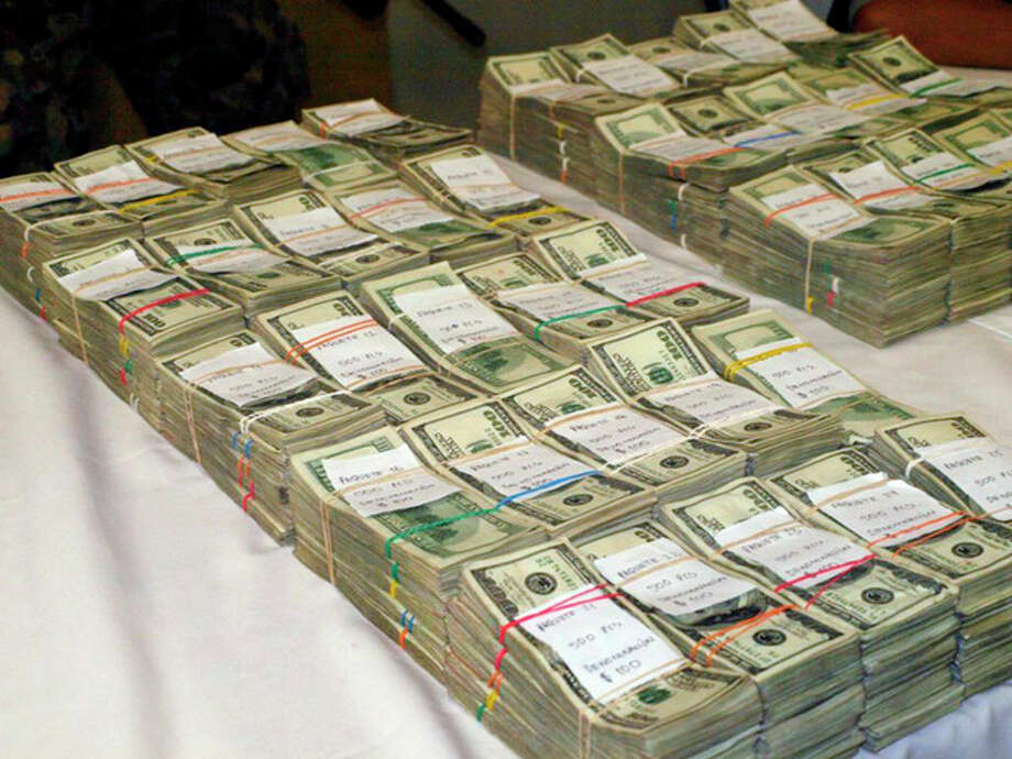 This undated photo, provided by U.S. Immigrations and Customs Enforcement (ICE), shows bulk cash seized during a combined ICE and Homeland Security Investigation (HSI) operation. Immigration agents report a rising number of cash seizures and arrests in the past half-dozen years as criminals, sidestepping scrutiny from banks over electronic transfers, resort to using cash to conceal proceeds from drug trafficking as they move the money south to crime rings in Mexico and elsewhere. (AP Photo/ICE) / ICE
