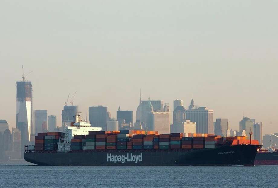 In this photo of Feb. 4, 2012, a cargo ship, owned by German shipping company Hapag-Lloyd, crosses New York Harbor. The U.S. trade deficit widened in December, reflecting a jump in imports of autos and industrial machinery. For the year, the deficit climbed to the highest level since 2008 as both exports and imports rose to all-time highs. (AP Photo/Mark Lennihan) / AP