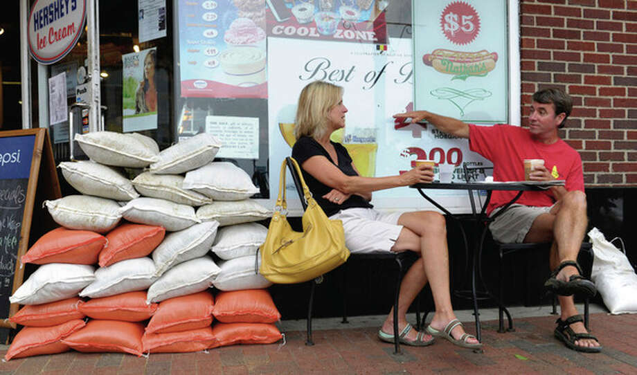 Jim and Amy Burdick of Annapolis, Md., drink coffee in downtown Annapolis next to a pile of sandbags as the town prepares for the arrival of Hurricane Irene Saturday, Aug. 27, 2011. (AP Photo/Susan Walsh) / AP