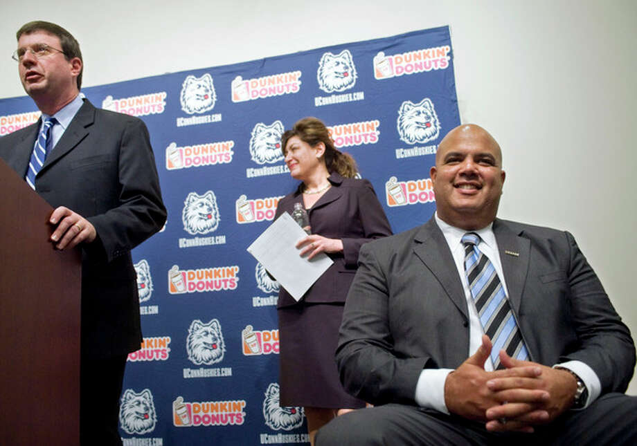Warde Manuel, right, smiles as sports information director Mike Enright, left, and university president Susan Herbst, center, announce Manuel as the new athletic director for the University of Connecticut at a news conference in Storrs, Conn., Monday, Feb. 13, 2012. (AP Photo/Jessica Hill) / AP2012