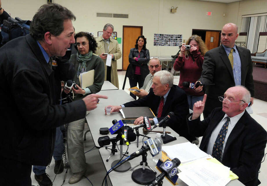 Former councilman Ken McKay, left, explodes in anger at police commissioner Frederick Brow, right, at the end of their meeting Tuesday Jan. 31, 2012. The East Haven Police Commission met Tuesday to determine whether to fire Police Chief Leonard Gallo. The commissioners in East Haven voted unanimously Tuesday to recommend that the mayor fire the police chief instead of letting him retire amid allegations that officers abused Latinos. (AP Photo/Mara Lavitt, New Haven Register) 1/31/12 / New Haven Register
