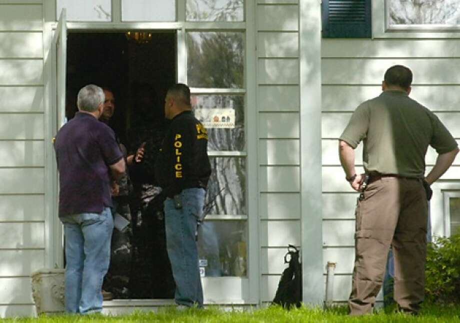 Norwalk Poliice Special Services Division officers and federal ATF agents raided a home on 24 Granite St. in Norwalk THursday morning. Hour photo / Erik Trautmann