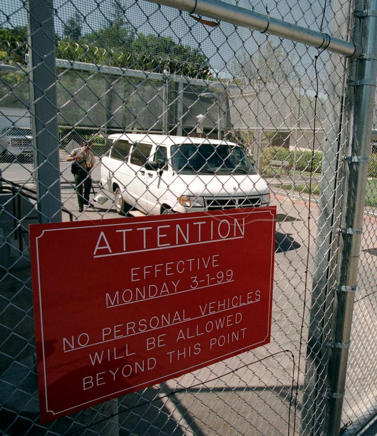 A security officer uses a mirror to check under a van as it departs Napa State Hospital in 1999. California's oldest psychiatric facility is seeing a spike in coronavirus cases.