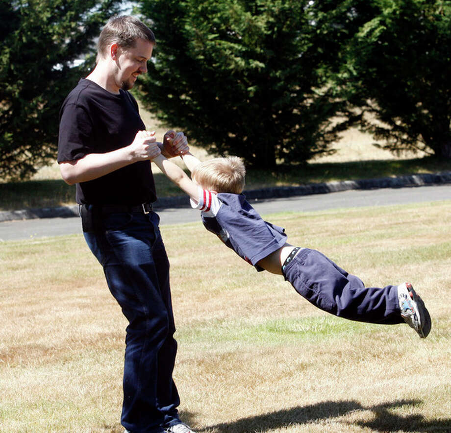In this Aug. 19, 2011 photo, Josh Powell plays with his son Braden in a park near his home, in Puyallup, Wash. Powell had long been a person of interest in his wife's disappearance from their home in West Valley City, Utah, two years ago. When Powell's two sons arrived Sunday, Feb. 5, 2012, for a court-ordered, supervised child custody visit with their father, Powell barred a social worker from entering and then torched the house. All three died. (AP Photo/The Salt Lake Tribune, Rick Egan) DESERET NEWS OUT; LOCAL TV OUT; MAGS OUT; MANDATORY CREDIT / The Salt Lake Tribune