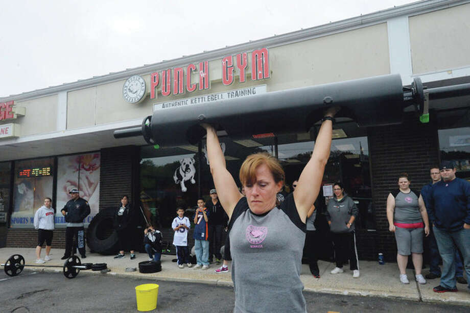 Hour photo / Matthew Vinci Maureen Hines lifts a 70-pound log at the Punch Kettlebell Gym in Norwalk Sunday during the strongwoman competition held to benefit the Bennett Cancer Center at Stamford Hospital. / (C)2011, The Hour Newspapers, all rights reserved