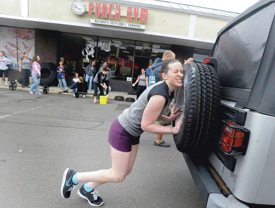 Hour photos / Matthew Vinci Julie Choiniere pushes a Jeep Wrangler across the parking lot of the Punch Kettlebell Gym in Norwalk Sunday for the strongwoman competition to benefit the Bennett Cancer Center at Stamford Hospital. / (C)2011, The Hour Newspapers, all rights reserved