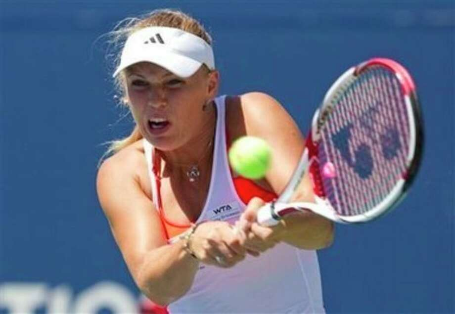 Caroline Wozniacki of Denmark, hits a return during her match against Roberta Vinci of Italy, at the Rogers Cup women's tennis tournament in Toronto on Wednesday, Aug. 10, 2011. (AP Photo/The Canadian Press, Darren Calabrese) / AP2011