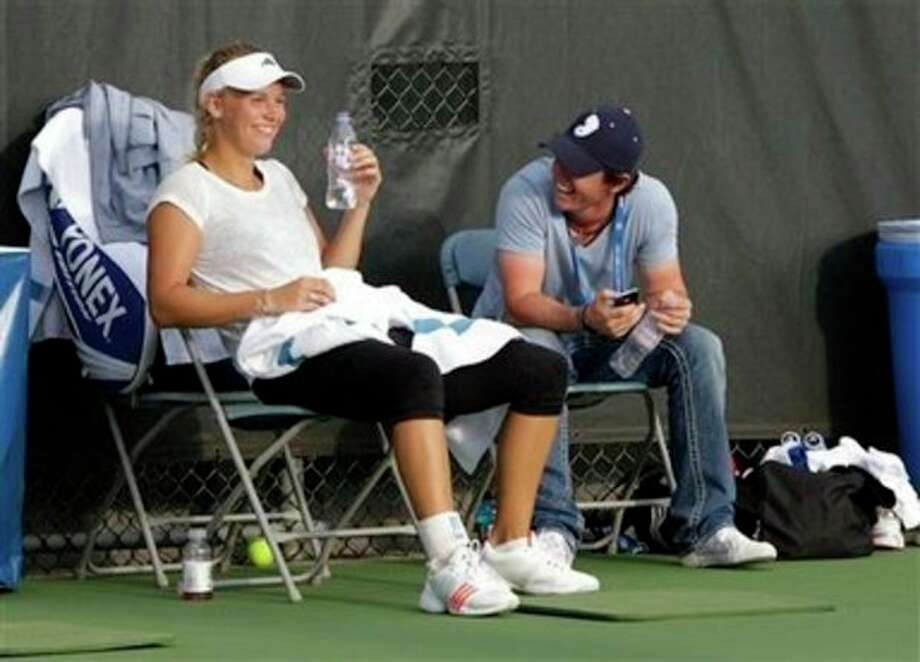 Golfer Rory McIlroy, from Northern Ireland, talks with top seeded Caroline Wozniacki, from Denmark, during her practice session at the Western and Southern Open, Sunday, Aug. 14, 2011 in Mason, Ohio. (AP Photo/Al Behrman) / AP