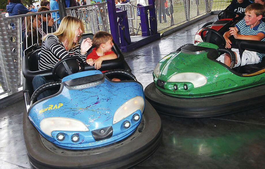 Photo/Alex von Kleydorff. Tasha Nagler behind the wheel with 6yr old son Edward try to beat the traffic in the Bumper cars at the Oyster Festival Sunday afternoon. / © 2010 The Hour Newspapers/Alex von Kleydorff