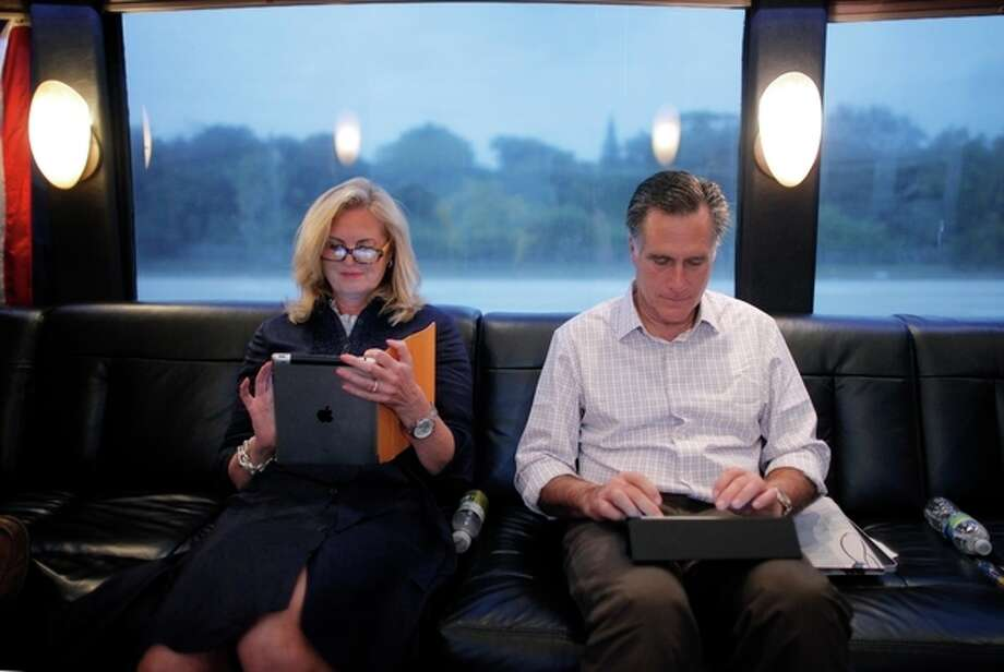 "FILE- In this Jan. 29, 2012, file photo, Republican presidential candidate, former Massachusetts Gov. Mitt Romney, and his wife Ann work on their iPads on their campaign bus as it travels to Hialeah, Fla. The spotlight on Ann Romney is getting brighter. Two out of three voters still don't know the wife of the presumptive Republican presidential nominee. But her profile is growing as Mitt Romney moves into the general election against President Barack Obama. She was a stay-at-home mother of five boys. She bakes cookies. And, at 63, she has 16 grandchildren who call her ""Mamie."" But don't be fooled: Republicans and Democrats alike see Ann Romney as an effective political weapon. (AP Photo/Charles Dharapak, File) / AP"