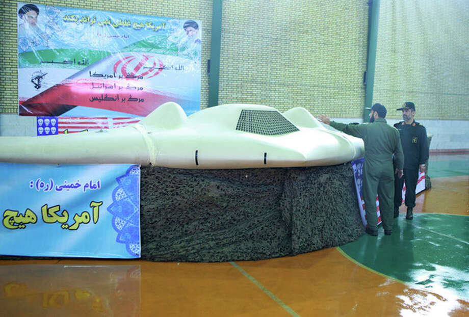 FILE - This file photo released on Thursday, Dec. 8, 2011, by the Iranian Revolutionary Guards, claims to show US RQ-170 Sentinel drone which Tehran says its forces downed earlier this week, as the chief of the aerospace division of Iran's Revolutionary Guards, Gen. Amir Ali Hajizadeh, right, listens to an unidentified colonel, in an undisclosed location, Iran. Iran's semiofficial Fars news agency said Thursday, April 18, 2012 that Russia and China have asked Tehran to provide them with information on a U.S. drone captured by the Islamic Republic in December. (AP Photo/Sepahnews, File) EDS NOTE: THE ASSOCIATED PRESS HAS NO WAY OF INDEPENDENTLY VERIFYING THE CONTENT, LOCATION OR DATE OF THIS IMAGE. / AP