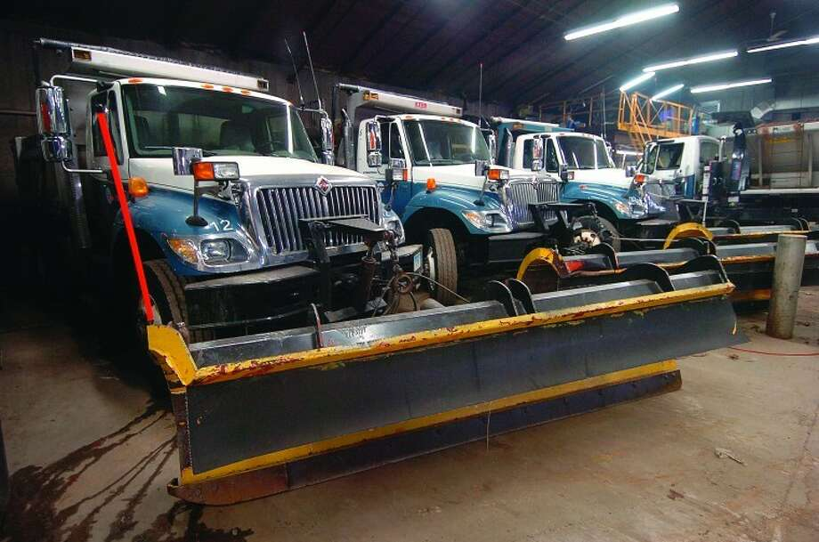 Hour Photo/ Alex von Kleydorff. Trucks with plows attached sit inside the DPW garage in Wilton.