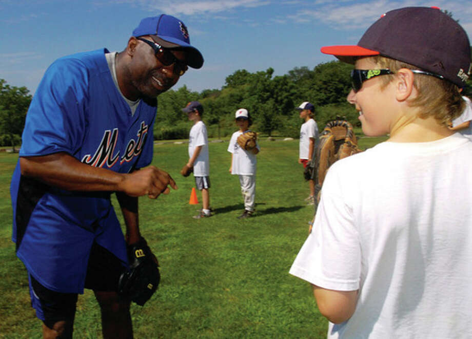 Hour Photo/Erik Trautmann Former New York Mets baseball player and current coach Mookie Wilson, left, works with campers including 9-year-old John Reynolds at Baseball WorldÕs final camp of the summer on Wednesday. / (C)2011, The Hour Newspapers, all rights reserved