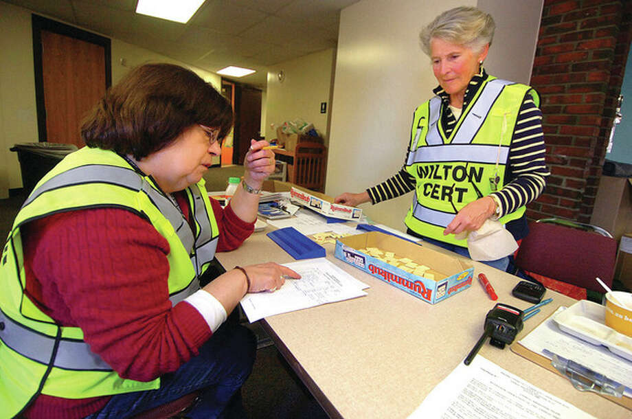 Hour Photo/ Alex von Kleydorff. L-R Linda Fein and Gail Reifsnyder volunteers with CERT sign in residents and get board games ready at the Emergency Shelter set up at Miller Driscoll school in Wilton. / 2011 The Hour Newspapers