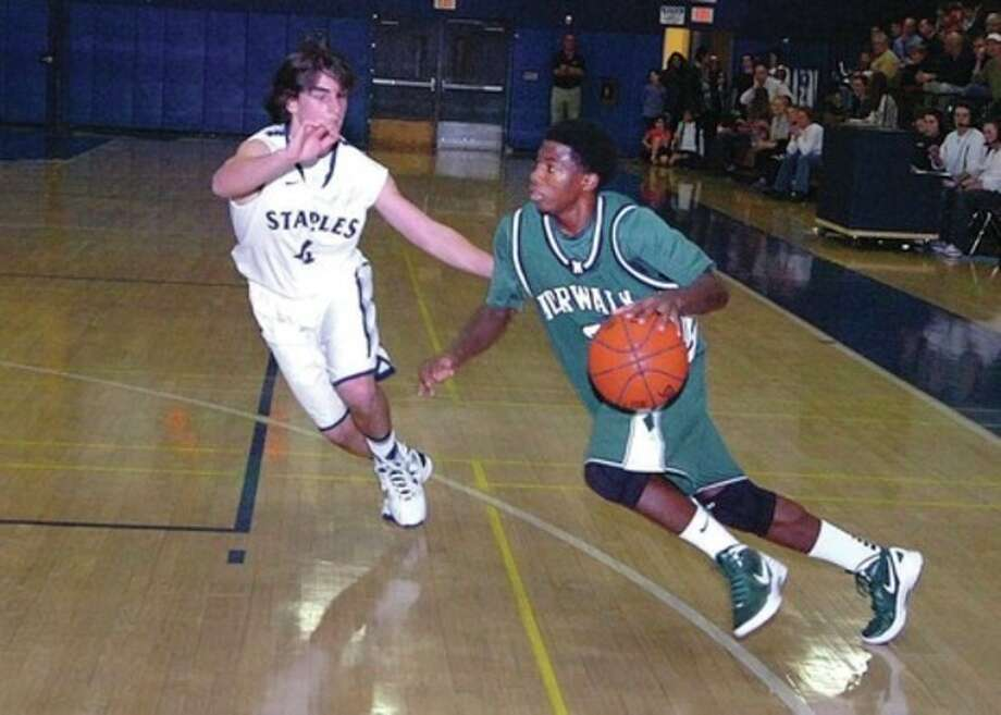 Hour Photo/Alex von Kleydorff Norwalk's Rasheen Thompson drives past James Frusciante of Staples during Wednesday night's game in Westport. Thompson tossed in 13 points and the Bears downed the Wreckers, 59-49, in the season-opener for both squads. / 2011 The Hour Newspapers