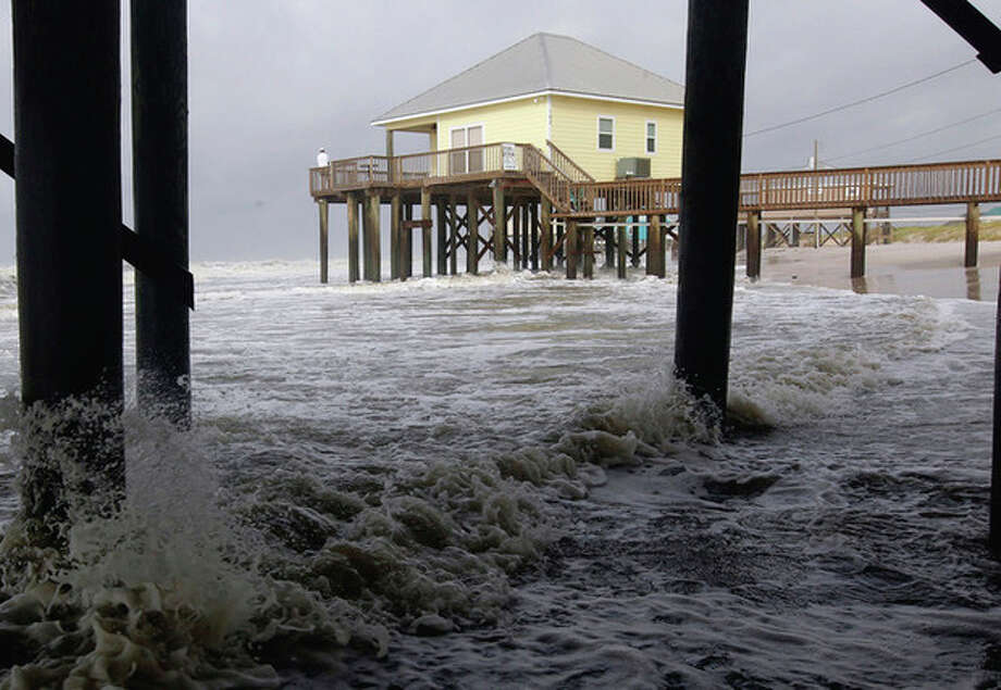 AP Photo/Dave Martin High surf rushes under houses along the west end of Dauphin Island, Ala., early Sunday. Tropical Storm Lee is continuing to meander along the Gulf Coast bring torrential rains and flooding. / AP