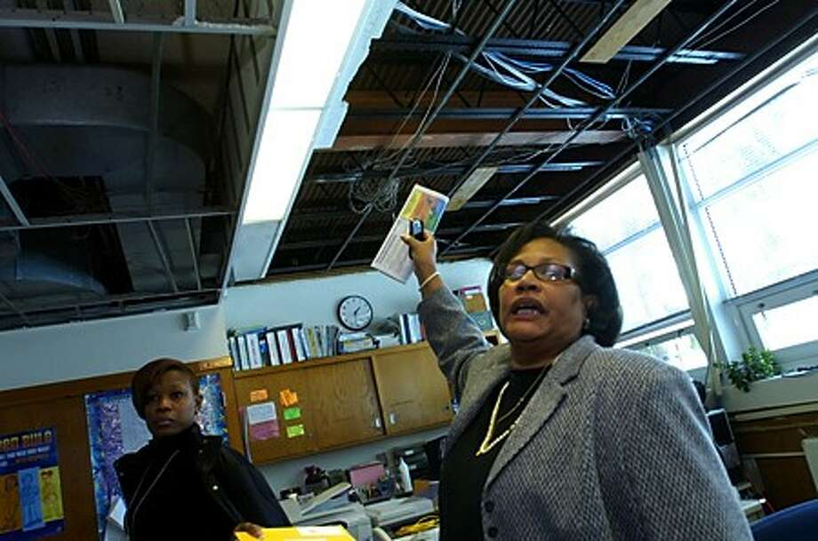 Ponus Ridge Middle School principal Dr.Linda Sumpter points out the damaged ceiling in the adminstrative offices while secretary Hope Holmes looks on. Last week a pipe burst on the school''s second floor and work is underway to repair adminstraive offices and 3 classrooms damaged by the flooding. Hour photo / Erik Trautmann
