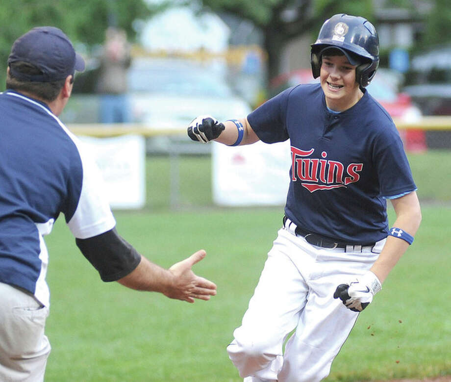 Photo by John Nash - Twins player Henry Hovland, right, prepares to slap hands with head coach John D'Elisa after hitting his second home run, a grand slam, in his team's 6-0 win over the Rangers in Tuesday night's Wilton Little League championship game.