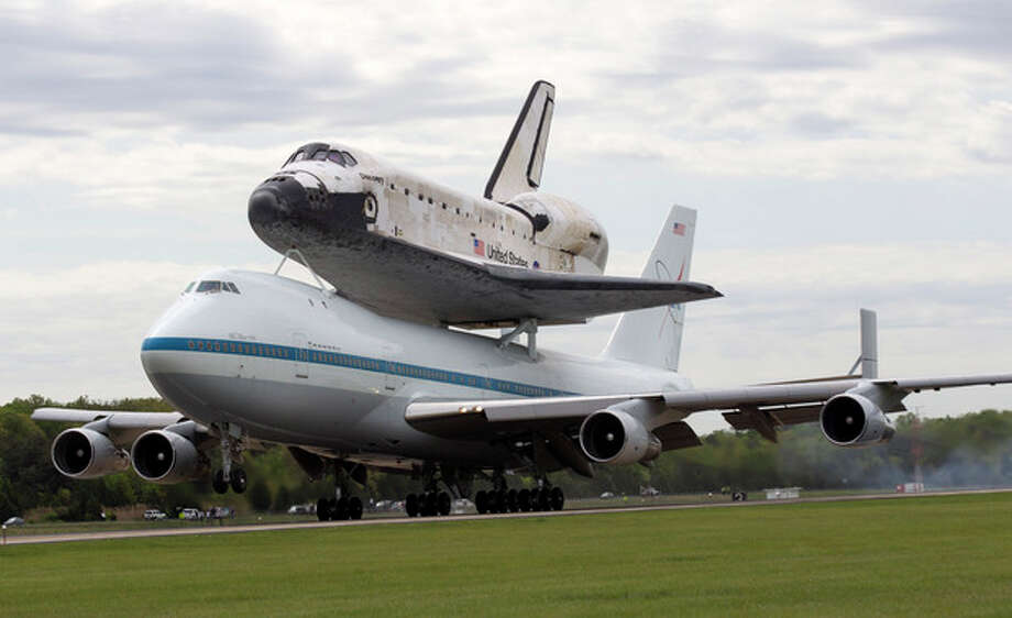 The space shuttle Discovery, sitting atop a 747 carrier aircraft, lands at Dulles International Airport in Chantilly, Va., Tuesday, April 17, 2012. Discovery, the longest-serving orbiter will be placed to its new home, the Smithsonian's National Air and Space Museum's Steven F. Udvar-Hazy Center in Chantilly, Va. (AP Photo/Manuel Balce Ceneta) / AP