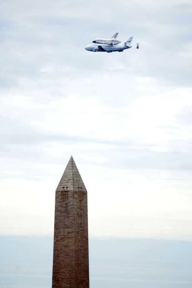 The Space Shuttle Discovery, attached to the back of a Boeing 747 airplane, passes over the Washington Monument, in Washington, Tuesday April 17, 2012. (AP Photo/Cliff Owen)