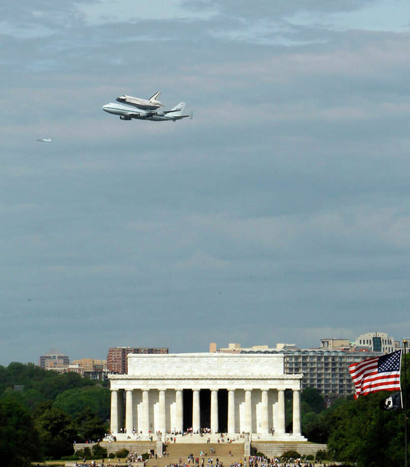 The Space Shuttle Discovery, mounted on the Shuttle Carrier Aircraft, flies over the Lincoln Memorial in Washington, Tuesday, April 17, 2012. Discovery is en route from Kennedy Space Center to the Smithsonian National Air and Space Museum Udvar/Hazy Center at Dulles International Airport. (AP Photo/Ann Heisenfelt) / FR13069 AP