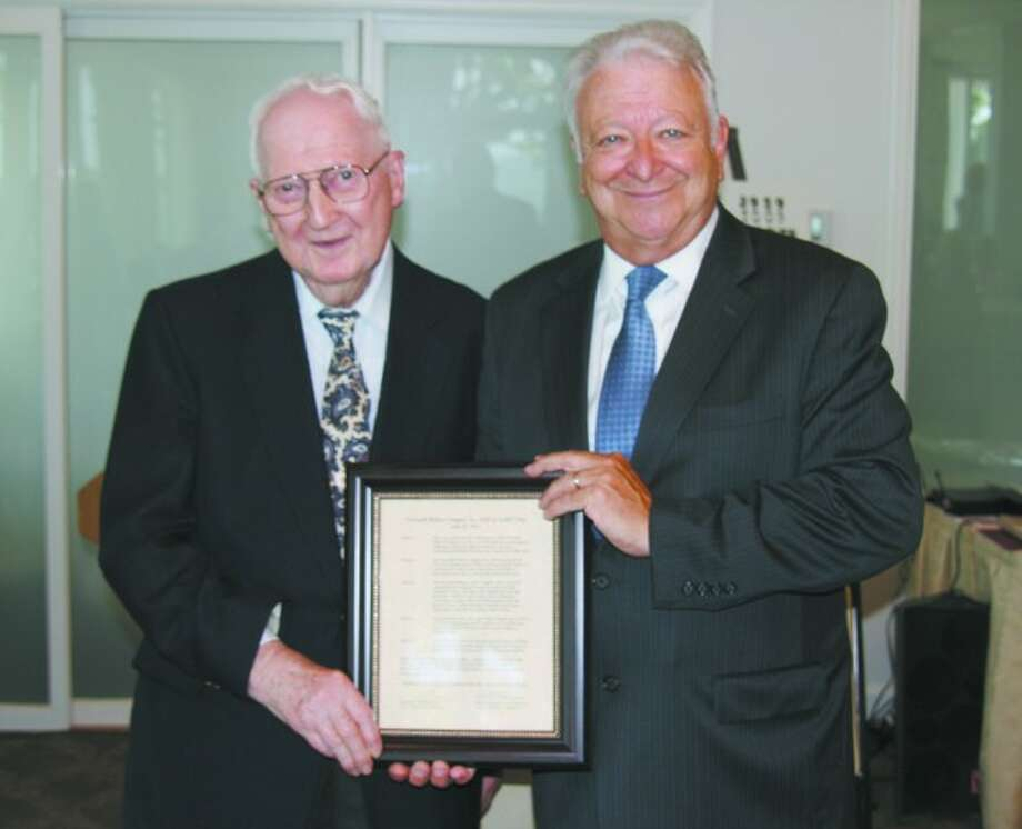 Abbott White, left, founder of Norwalk/Wilton AARP Chapter 3929, receives a framed proclamation from Norwalk Mayor Richard Moccia. The proclamation is in honor of the chapters 25th anniversary.