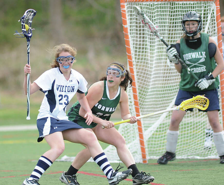 Hour photo/John NashWilton's Sara Dickinson, left, is defended by Norwalk's Victoria Price, center, as Bears goalie Megan Carney looks on during Tuesday's game at Kristine Lilly Field in Wilton. The host Warriors won, 17-7.