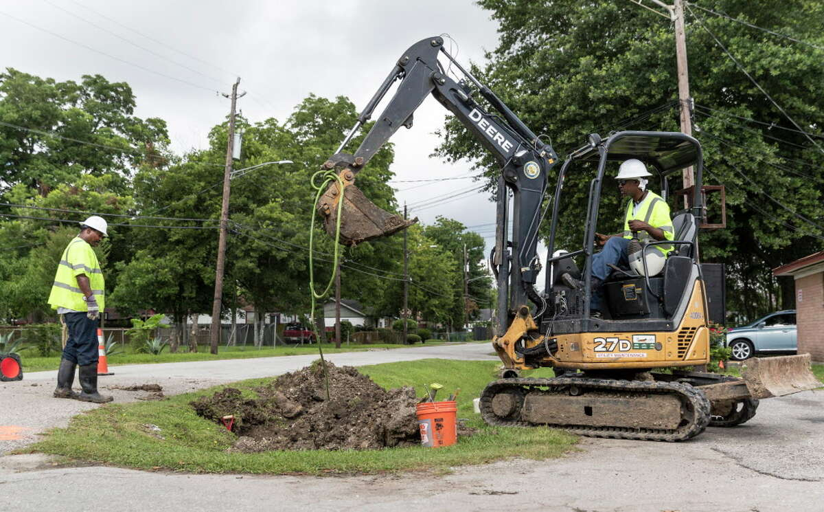 City of Houston Public Works employees Senora Behn (right), Michael Riggs (left) work to remove a Shot Line which was stuck in the main sewer line in the 5400 block of Pardee Street in Houston, TX on Saturday, June 11, 2016.