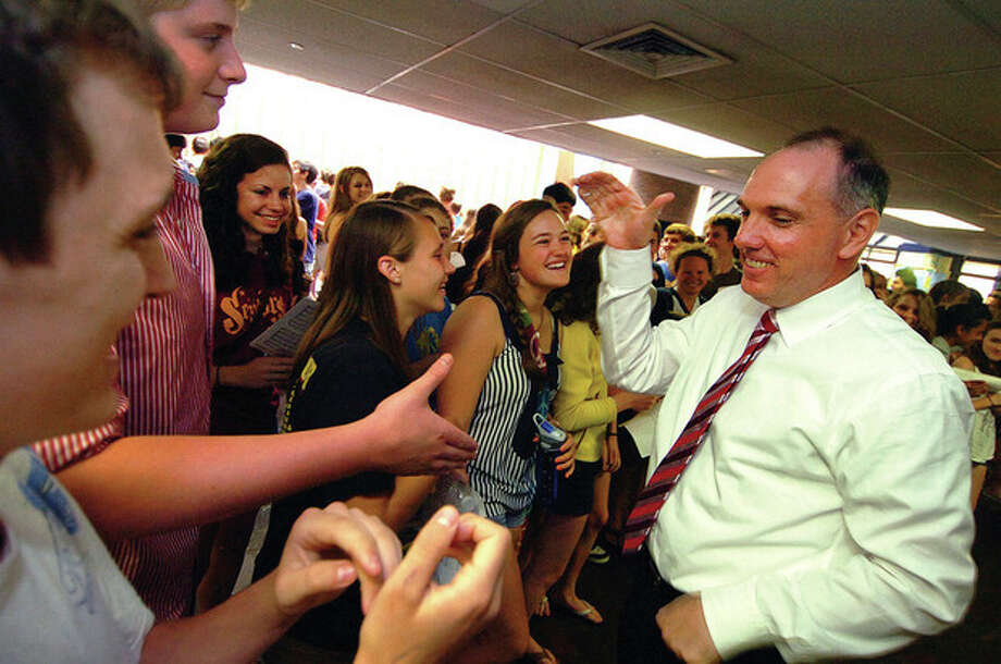 Photo by Alex von Kleydorff Wilton High School Principal Tim Canty gets some high fives from band and chorus members who suprised him by playing the Wilton fight song for him on the last day of school. / 2011 The Hour Newspapers