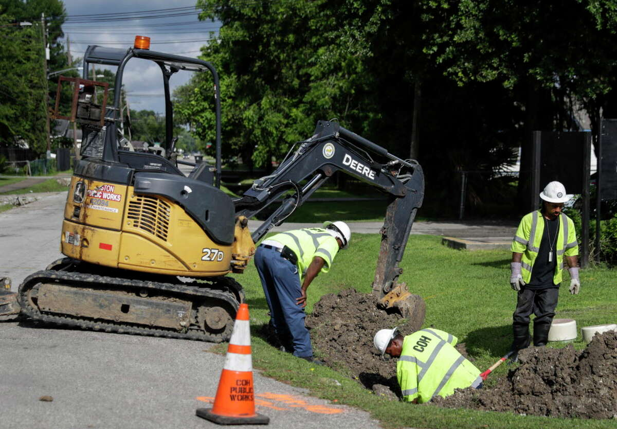 City of Houston Public Works employees (left to right) Senora Behn, Michael Riggs, and Arie Nelson work to repair a sewer line in the 5400 block of Pardee Street in Houston, TX on Saturday, June 11, 2016.