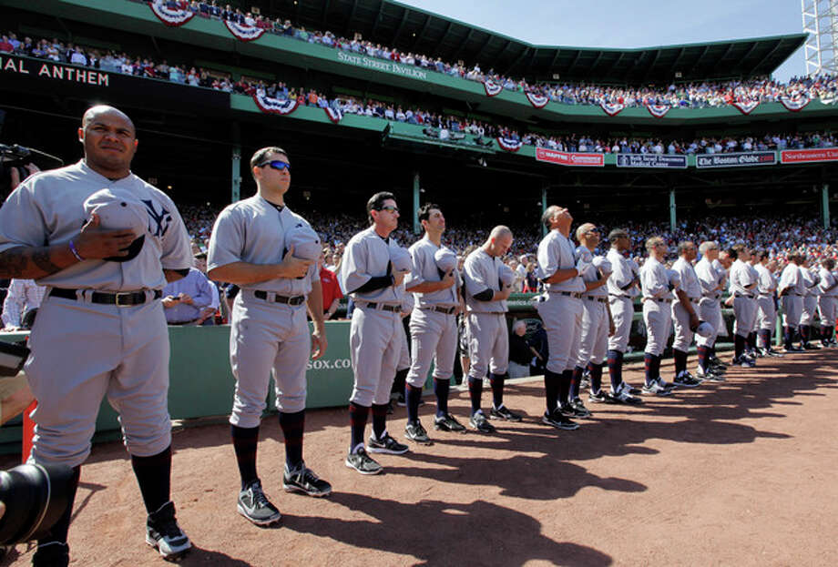 New York Yankees players stand for the national anthem in throw-back uniforms prior to a baseball game against the Boston Red Sox at Fenway Park in Boston, Friday, April 20, 2012, during a celebration of the 100th anniversary of the first regular-season game at the ball park. (AP Photo/Elise Amendola) / Copyright: The Associate Press