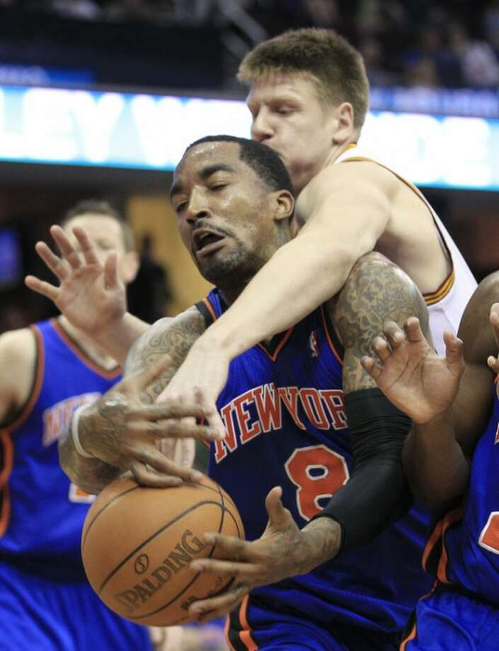 Cleveland Cavaliers' Luke Harangody, top, and New York Knicks' J.R. Smith battle for a rebound in the second quarter in an NBA basketball game on Friday, April 20, 2012, in Cleveland. (AP Photo/Tony Dejak)