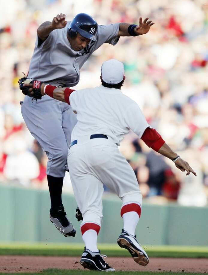 Boston Red Sox's Mike Aviles, right, tags out New York Yankees' Raul Ibanez in a rundown in the eighth inning of a baseball game in Boston, Friday, April 20, 2012. (AP Photo/Michael Dwyer)
