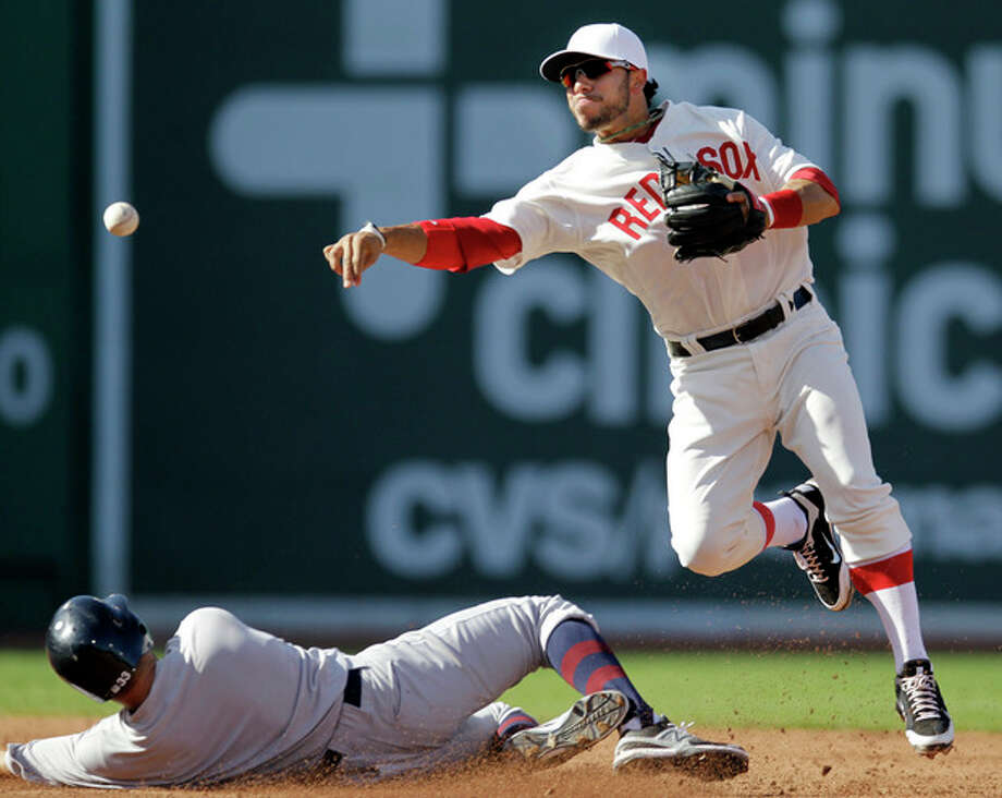 New York Yankees' Nick Swisher, left, is out at second as Boston Red Sox shortstop Mike Aviles, right, turns a double play on Yankees' Raul Ibanez in the third inning of a baseball game at Fenway Park in Boston, Friday, April 20, 2012. (AP Photo/Elise Amendola) / AP
