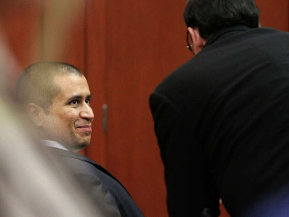 George Zimmerman smiles with a member of his defense team after he was granted bond, Friday, April 20, 2012, during a hearing in Sanford, Fla. Circuit Judge Kenneth Lester says Zimmerman can be released on $150,000 bail as he awaits trial for the shooting death of Trayvon Martin. Zimmerman is charged with second-degree murder in the shooting of Martin. He claims self-defense. (AP Photo/Orlando Sentinel, Gary W. Green, Pool) / POOL Orlando Sentinel