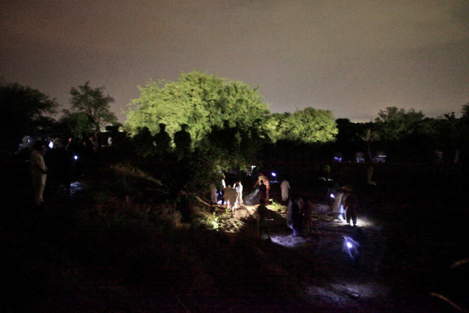 Pakistani rescue workers and civilians look for survivors of a plane crash in a field on the outskirts of Islamabad, Pakistan, Friday, April 20, 2012. A Pakistani passenger jet with 127 people on board crashed into wheat fields Friday as it was trying to land in a thunder storm at an airport near the capital Islamabad. Sobbing relatives of those on the flight flocked to the airport, and officials said there appeared to be no survivors. (AP Photo/Muhammed Muheisen) / AP