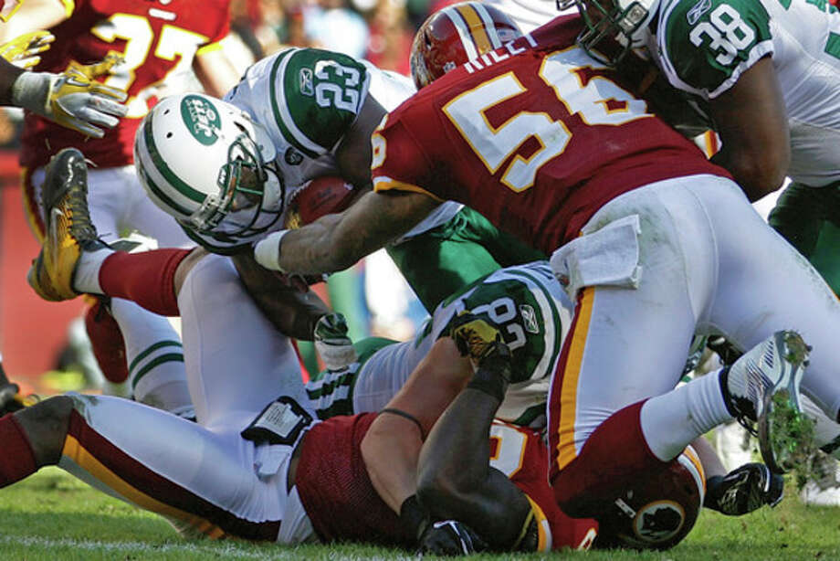 New York Jets running back Shonn Greene (23) powers his way into the end zone past Washington Redskins inside linebacker Perry Riley (56) for a touchdown during the first half of an NFL football game in Landover, Md., Sunday, Dec. 4, 2011. (AP Photo/Evan Vucci) / AP