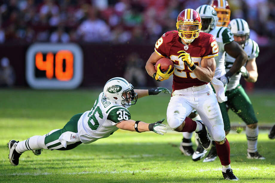 Washington Redskins running back Roy Helu runs out of the grasp of New York Jets strong safety Jim Leonhard (36) during the first half of an NFL football game in Landover, Md., Sunday, Dec. 4, 2011. (AP Photo/Nick Wass) / FR67404 AP
