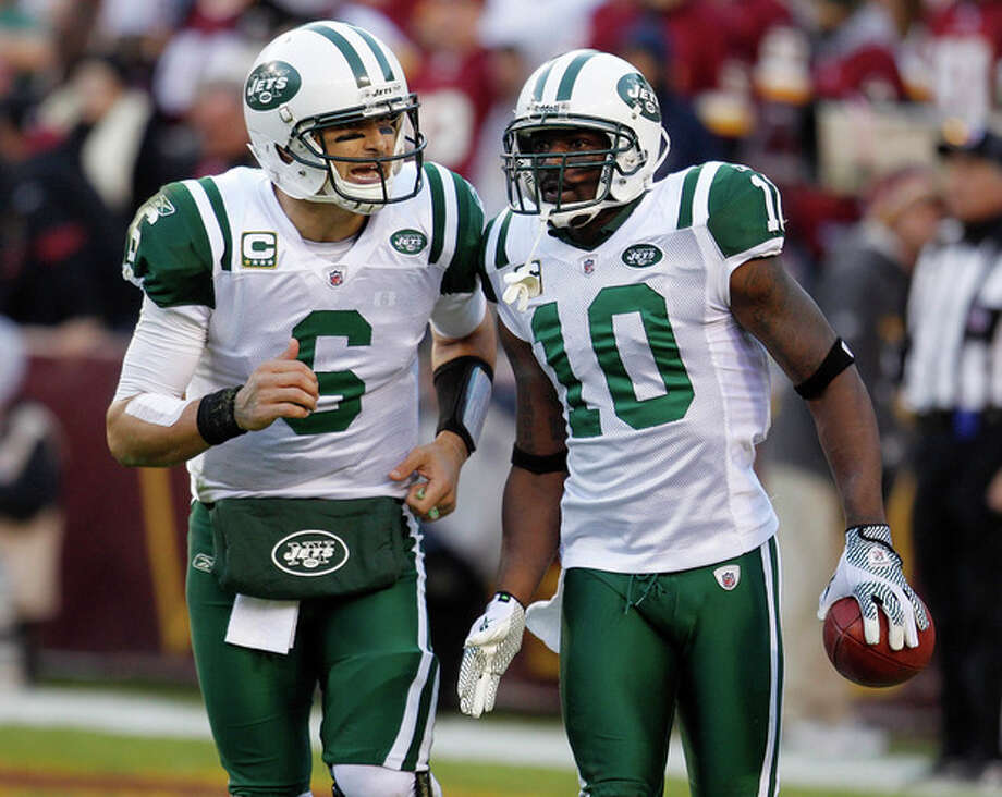 New York Jets wide receiver Santonio Holmes, right, runs off the field with quarterback Mark Sanchez after scoring a touchdown on a pass from Sanchez during the second half of an NFL football game against the Washington Redsk insin Landover, Md., Sunday, Dec. 4, 2011. (AP Photo/Evan Vucci) / AP