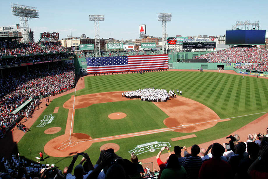 Former Boston Red Sox team member gather on the field while the National Anthem is played during ceremonies to celebrate the 100th anniversary of Fenway Park before a baseball game between the New York Yankees and the Boston Red Sox in Boston, Friday, April 20, 2012. (AP Photo/Michael Dwyer) / AP