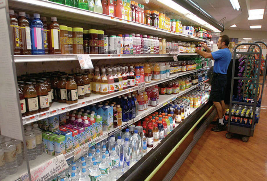 Pepsi sales representative Paul Freitas stock shelves in the cold beverage section of Village Market in Wilton. There is a petition to sell beer in grocery stores that may be on the Nov. 8 ballot. / (C)2011, The Hour Newspapers, all rights reserved