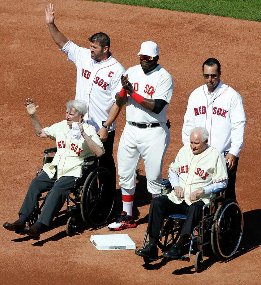 Former Boston Red Sox catcher Jason Varitek, top left, stands with, current designated hitter David Ortiz, top center, former pitcher Tim Wakefield, top right, and former players Bobby Doerr, seated right, and Johnny Pesky, seated left, on the field during ceremonies to celebrate the 100th anniversary of a regular season baseball game at Fenway Park before the game between the New York Yankees and the Red Sox in Boston, Friday, April 20, 2012. (AP Photo/Michael Dwyer) / AP