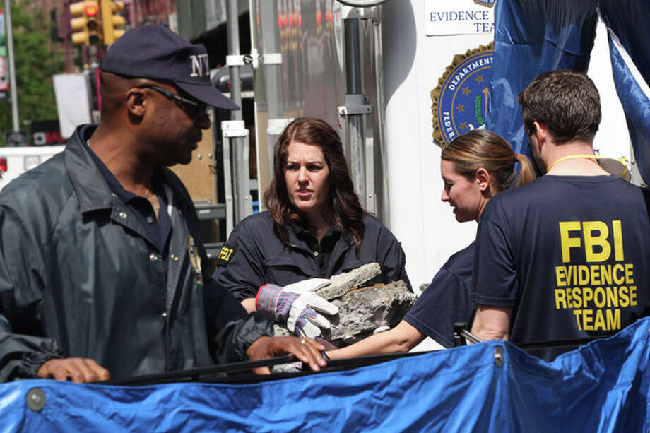 Members of the FBI team carry pieces of concrete out of a basement of a building on the corner of Wooster Street and Prince Street in Manhattan during a renewed investigation into the 1979 disappearance of 6-year-old Etan Patz, on Friday, April 20, 2012 in New York. Patz vanished after leaving his family's home for a short walk to his school bus stop. NYPD spokesman Paul Browne says the building being searched for his remains is about a block from where the family lived. (AP Photo/Mary Altaffer) / AP
