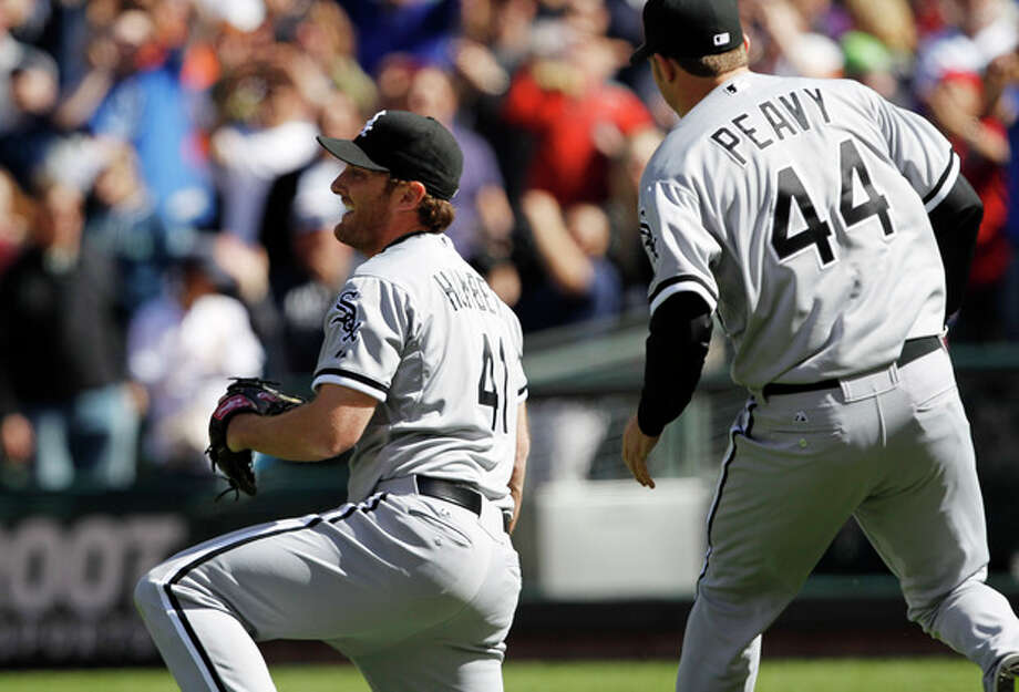 Chicago White Sox starting pitcher Philip Humber, left, reacts after pitching a perfect baseball game against the Seattle Mariners, Saturday, April 21, 2012, in Seattle. The White Sox won 4-0. (AP Photo/Elaine Thompson) / AP