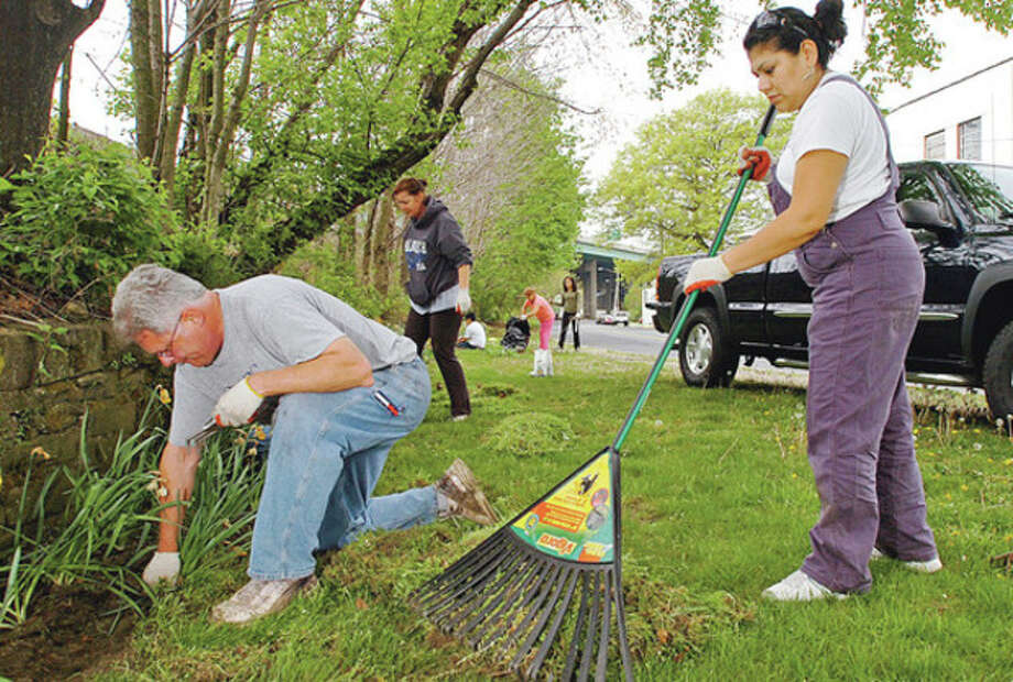Stamford residents Chad Well er and Adrianna Lugo clean up along East Main St as part of the East Side Neighborhood Clean Up and Planting event Saturday morning sponsored by the East Side Partnership and Domus.Hour photo / Erik Trautmann / (C)2011, The Hour Newspapers, all rights reserved