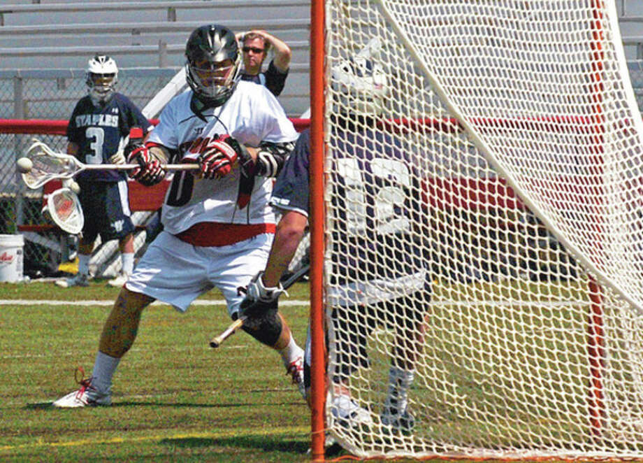 Hour photo/Erik TrautmannNew Canaan's Peter Kraus lets fly with a shot that became the second goal of the second quarter of Saturday's game against Staples. Kraus had two goals and four assists in the Rams' 11-5 victory. / (C)2011, The Hour Newspapers, all rights reserved