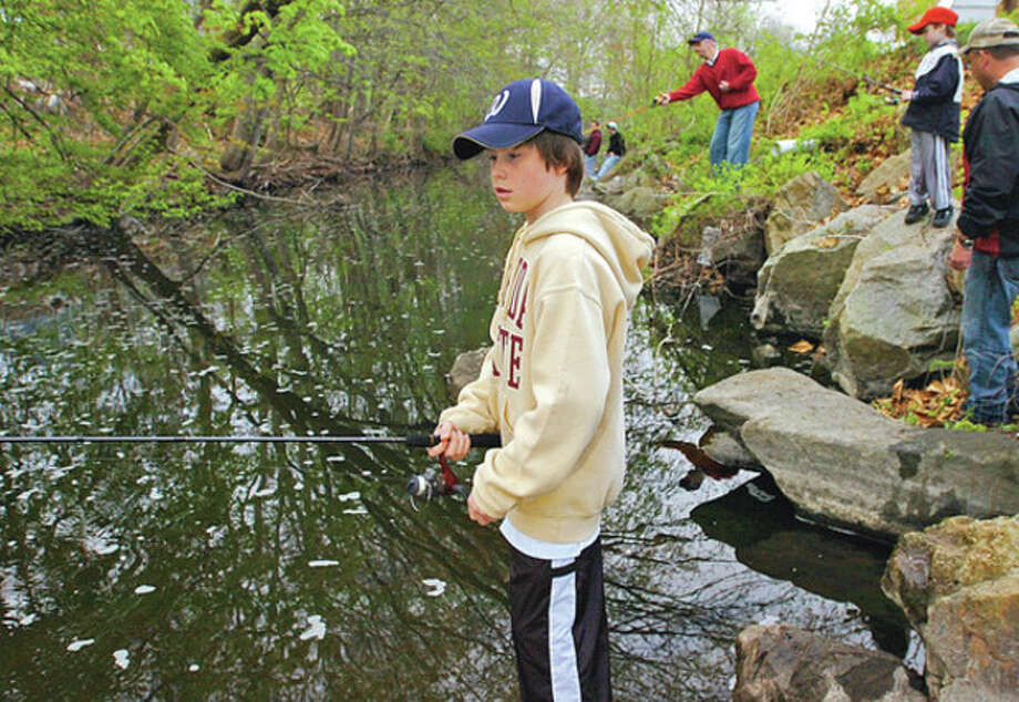 Zach Liston, 11, fishes on the Norwalk River in Wilton on Saturday. / (C)2011, The Hour Newspapers, all rights reserved