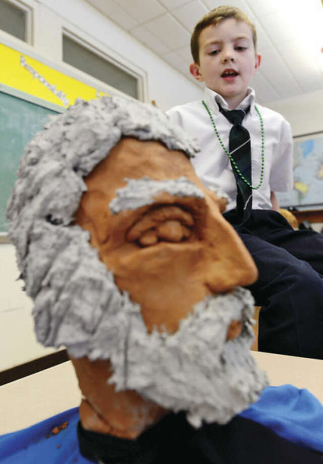 Jason Mitchell made a bust of Frederick Douglas and gives his report on the black historical figure during Elizabeth Williams All Saints Catholic School 3rd grade class in honor of Black History month Tuesday.