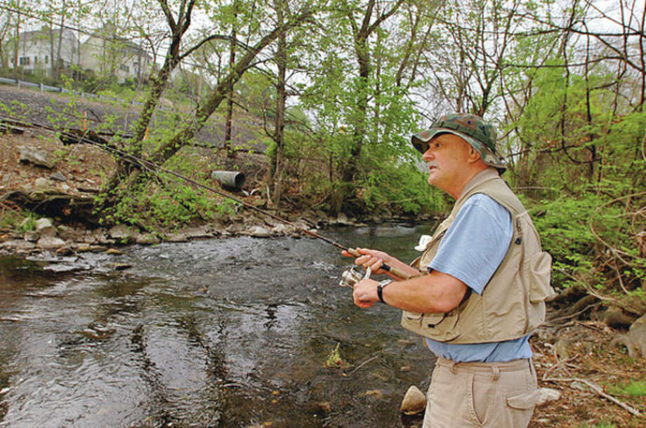 Norwalk resident Richard Sigmund fishes on the Norwalk River in Wilton on opening day Saturday. / (C)2011, The Hour Newspapers, all rights reserved